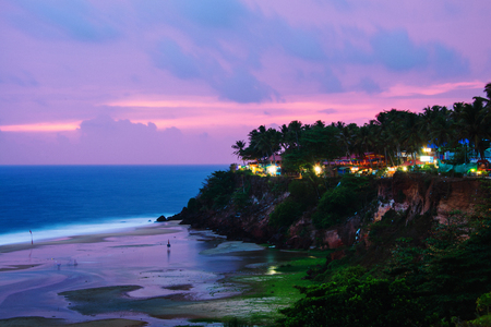 Kerala, India. Varkala beach at night, various cafes and restaurants at the cliff with colorful sunset sky and motion blurred Laccadive Sea and Papanasam beach in Kerala, India