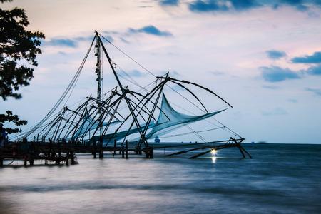 ケララ, インド.コーチン、ケララ州、インド夕暮れ時の中国フィッシュ ネットの時間経過。カラフルな曇り空