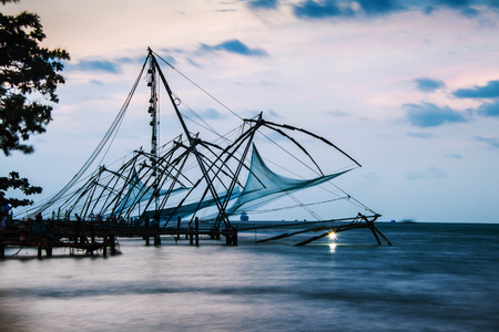 Kerala, India. Time-lapse of Chinese fishnets in Cochin, Kerala, India at sunset. Colorful cloudy sky
