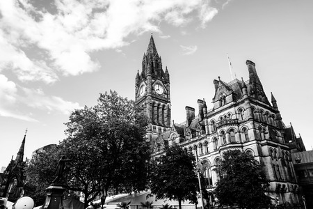 Manchester, UK. Town Hall of Manchester, UK with cloudy sky during the sunny day. Black and white