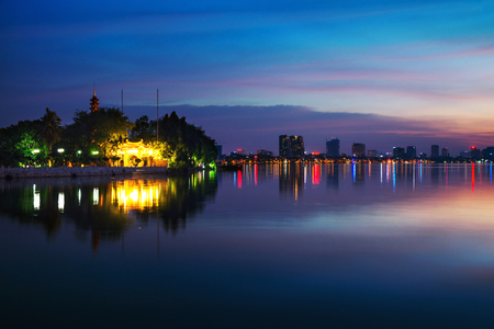 Hanoi, Vietnam. Tran Quoc Pagoda the oldest Buddhist temple in Hanoi, Vietnam. Located on a small island in West Lake. Dark colorful sky at sunset Banco de Imagens