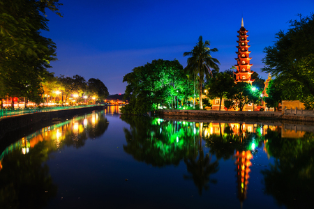 Hanoi, Vietnam. Tran Quoc Pagoda the oldest Buddhist temple in Hanoi, Vietnam. Located on a small island in West Lake. Dark colorful sky at sunset Stock Photo