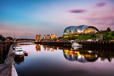 Newcastle upon Tyne, UK. Famous Millennium bridge at sunset. Illuminated landmarks with river Tyne in Newcastle, UK and colorful sky Stock Photo