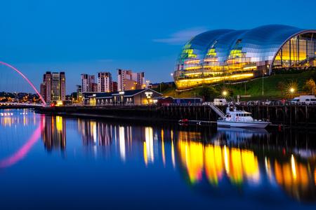 Newcastle upon Tyne, UK. Famous Millennium bridge at night. Illuminated landmarks with river Tyne in Newcastle, UK and clear blue sky Stock Photo - 101172435