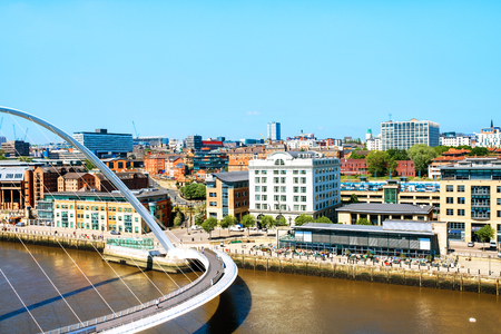 Newcastle upon Tyne, UK. Millennium bridge during the sunny day in Newcastle, UK. Aerial view of bridge with historical buildings at the background Stock Photo