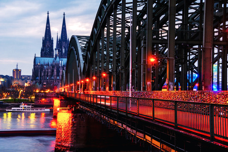 Cloudy day view of Cathedral and illuminated Hohenzollern bridge in Cologne, Germany