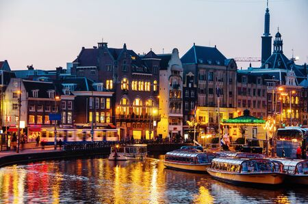 Amsterdam, Netherlands. Illuminated buildings in the center of Amsterdam, Netherlands at night. Reflection in canal, many boats, restaurants and cafes