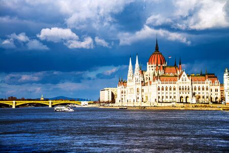 Budapest, Hungary. A view over the the Parliament and river Danube in Budapest, Hungary, on a warm summer day with a cloudy sky. Boats passing by Stock fotó