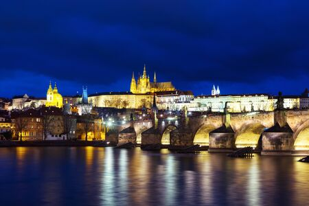 Prague, Czech Republic. Charles Bridge over Vltava river in Prague, Czech Republic at night. View of illuminated castle with cloudy sky