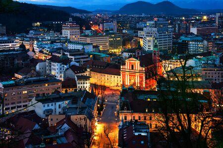 Ljubljana, Slovenia. Aerial view of Ljubljana, Slovenia city center. Illuminated Franciscan Church of the Annunciation and triple Bridge. Mountains at the background Archivio Fotografico