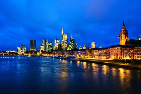 Skyline von Frankfurt, Deutschland im Sonnenuntergang mit berühmten beleuchteten Wolkenkratzern
