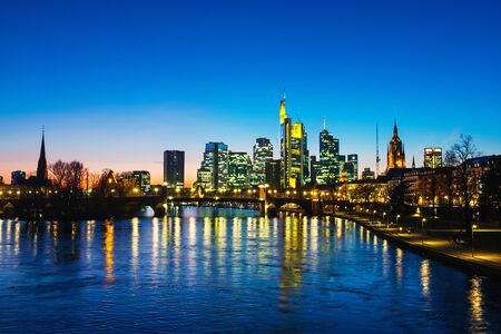 Frankfurt am Main, Germany. Skyline of Frankfurt, Germany in the sunset with famous illuminated skyscrapers and river at night