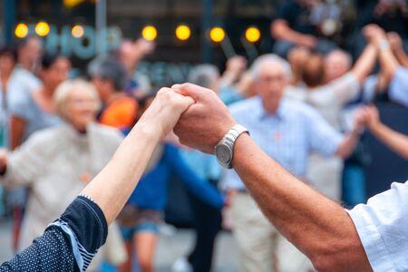 Blick auf ältere Menschen, die Händchen halten und den Nationaltanz Sardana tanzen? Standard-Bild