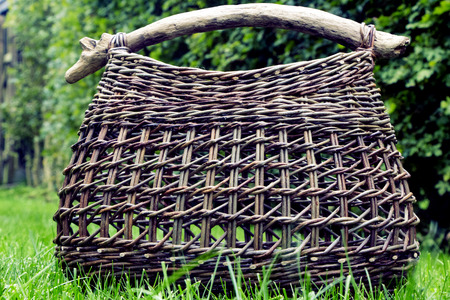 Basket of wicker on green grass on a sunny day. Фото со стока