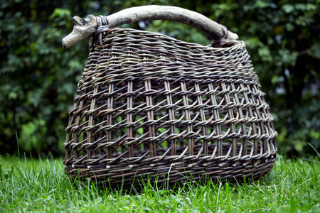 desk: Beautiful basket of wicker with a stick as handle.