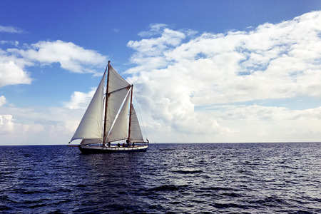 Vintage sail boat sailing on dark blue ocean under blue and cloudy sky. Фото со стока