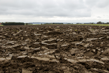 Dark brown dirt field on a cloudy day in autumn.