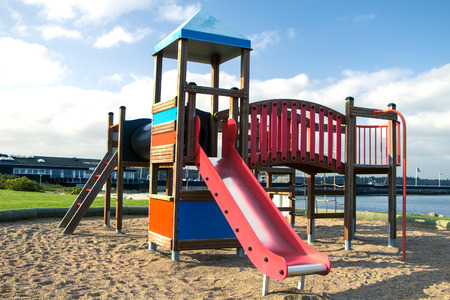 Wooden red and blue playground on sand on a sunny day.