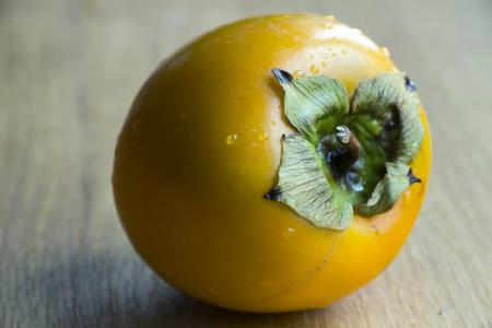 Fresh ripe orange persimmon on wooden background.