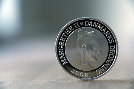 Danish silver coin with the danish queen on wooden table on a cloudy day.
