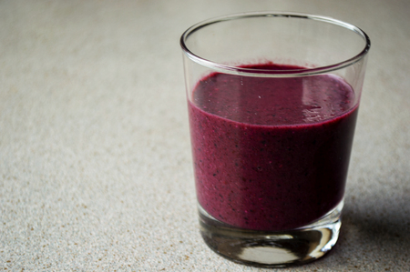Purple smoothie with berries and fruit in glass on a grey table. Фото со стока