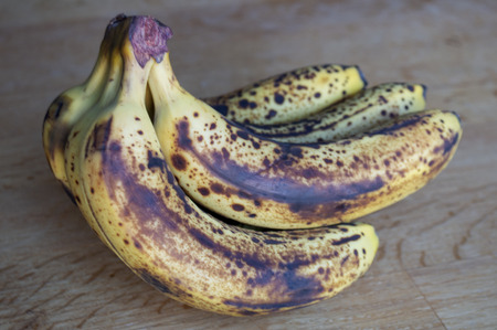 Bunch of ripe bananas on wooden background.