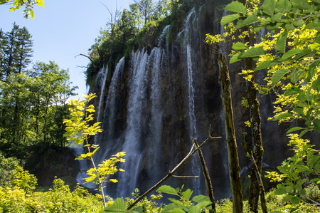 Big waterfall in Plitvice with trees in front and blue sky in background in summer.