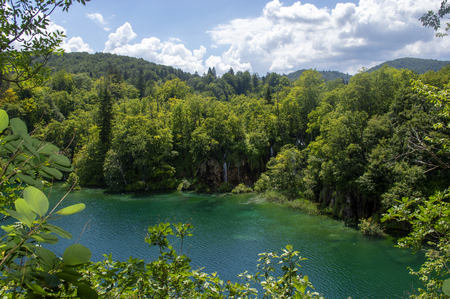 Landscape in Plitvice with green trees, a blue lake and a blue sky with clouds on a sunny day. Фото со стока