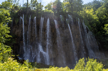 Big waterfalls and green trees in Plitvice in summer.