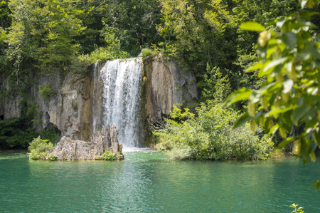 Beautiful waterfall, green trees and a blue lake in Plitvice tourist attraction. Фото со стока