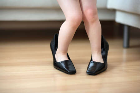 big girl: Little child wearing big shoes