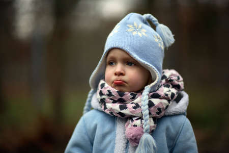 to sulk: A little girl in cold winter