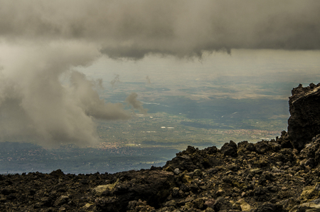 View of Sicilian territory between clouds from the top of Etna volcano Stock Photo