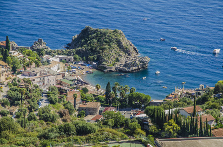 Bay with sandy beach and pier on the mediterranean at the height of the city of taormina sicily italy Stock Photo
