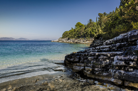 close-up of beach and calcareous rocks in a small and peaceful cove on the route and in the vicinity of the fiskardo village the turquoise sea in the background the mountains of kefalonia island