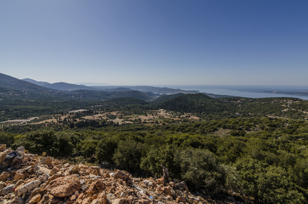 you see calcareous rocks and the territory of the island of kefalonia with its fields planted the mountains and in background the Ionian sea in the vicinity of the mouth of the bay of Argostoli to sea