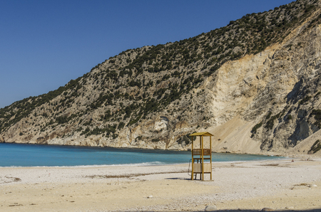 famous beach of Myrtos in Kefalonia with the mountains that plummet and lifeguard box to help fight the strong waves that turn the calcareous stones into dust