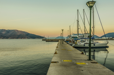 dock and sailboats moored to it then the Ionian sea and finally the mountains at sunrise over Sami harbor on the island of Kefalonia Greece