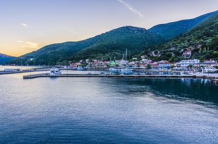 Panoramic view from the sea of the port of Sami with its moorings the port facilities and back the mountains illuminated by the sunset sun Kefalonia Stock Photo