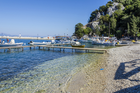 small wooden dock for boats and sports boats on the beach near the port of frikes ithaka and in the background the mountain that falls into the sea Stock Photo