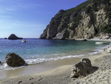 Lonely beach only accessible by boat between cliffs in the vicinity of the town of Palaiokastritsa on the island of Corfu Greece.