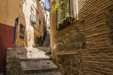 Medieval cobbled and stepped street with flowery balconies and public lighting lamps in the city of Toledo. Spain Archivio Fotografico
