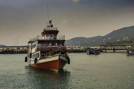 Typical passenger boat on the island of Koh Samui in the gulf of Thailand. Behind are the docks and other colorful small boats and finally the mountains of the island. Editorial
