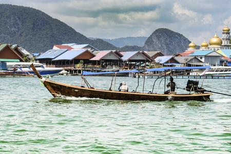 Taxi boat transporting passengers through the village of Koh Panyee Bay of Phang Nga. Phuket Thailand