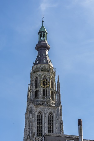detail tower of the old great church of breda with its colorful clock. holland netherlands