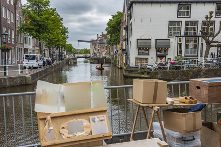 view of an alkmaar canal in the foreground a market business and in the background the canal with a boat carrying cheese and a drawbridge. netherlands holland