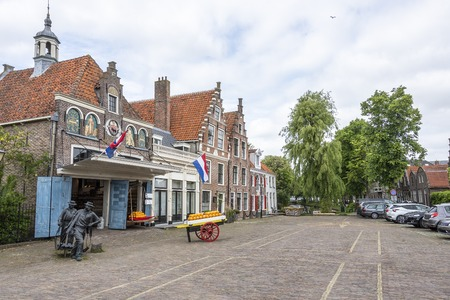 square with its traditional cheeses and houses and in the background a canal in the village of edam. netherlands