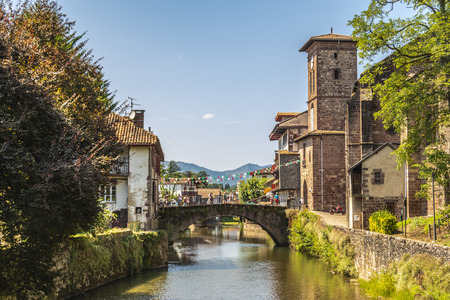 View of the river Nive on its way through the village of Saint Jean Pied de Port and in the background the Pyrenees. France. Stok Fotoğraf