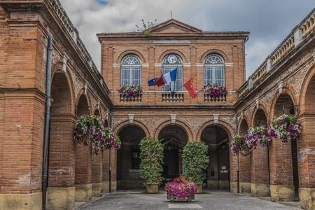 Facade of the town hall of Saint Ybars with its flags in the region of Midi-Pyrenees district of Pamiers. Ariege France Reklamní fotografie