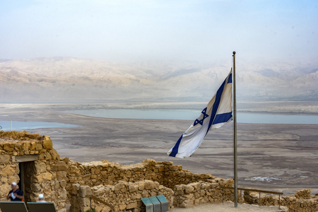 Israeli flag waving over the ruins of Masada and in the background the Judean desert and the Dead Sea.